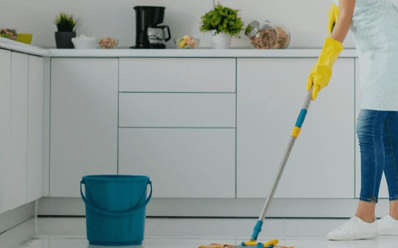 Femeie care da cu mopul in bucatarie