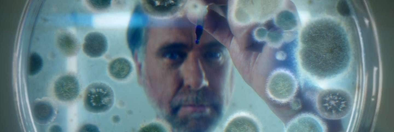 Barbat care se uita prin lupa la microbi